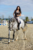 Woman astride a horse. Beautiful young woman riding a horse on a hippodrome Royalty Free Stock Photos