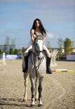 Woman astride a horse. Beautiful young woman riding a horse on a hippodrome Stock Photo