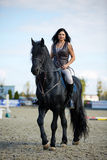 Woman astride a horse. Beautiful young woman riding a horse on a hippodrome Royalty Free Stock Image