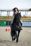 Woman astride a horse. Beautiful young woman riding a horse on a hippodrome Royalty Free Stock Photography
