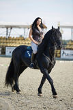 Woman astride a horse. Beautiful young woman riding a horse on a hippodrome Stock Photos