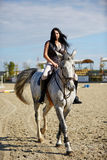 Woman astride a horse Royalty Free Stock Image