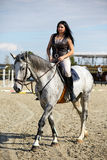 Woman astride a horse. Beautiful young woman riding a horse on a hippodrome Stock Photography