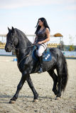 Woman astride a horse Stock Photos