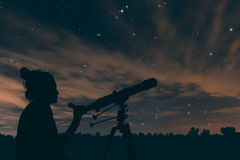 Woman with astronomical telescope. Night sky. Woman with astronomical telescope. Night sky, with clouds and constellations. Aquarius, Aguila. Scutum, Ophiuchus stock photo