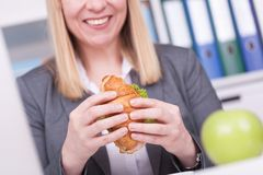 Free Woman At The Office Having Lunch. Concept For Healty Or Unhealthy Food At Work Royalty Free Stock Images - 140120119