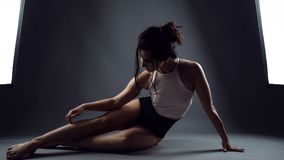 Woman athlete in black high-waist panties and white top sitting on the floor and touching her leg. Portrait of young woman athlete in black high-waist panties Stock Photos