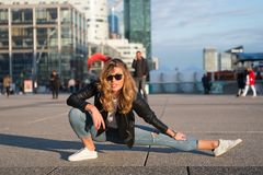 Woman athlete or dancer split leg in paris, france. Sensual woman with long hair in sunglasses and jeans, fashion. Yoga, pilates, Royalty Free Stock Images