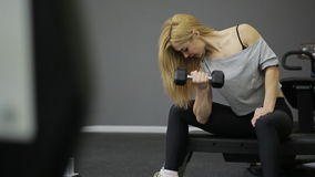 A woman athlete doing exercise on the biceps in stock footage