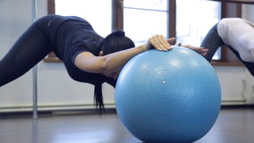 Woman athlete doing exercises on gym ball in fitness studio stock footage