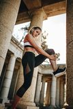 Woman athlete doing fitness workout taking support of a stone pillar. Fitness woman doing stretching workout of the legs royalty free stock image