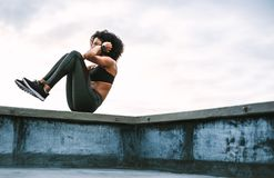 Woman athlete doing workout on rooftop stock photo