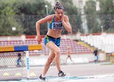 Woman Athlete falls at 3000 m Steeplechase Royalty Free Stock Image
