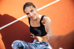 Woman athlete getting up and taking somebody hand on stadium. Smiling attractive young woman athlete getting up and taking somebody hand on stadium Royalty Free Stock Photo