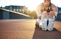 Woman athlete grabs her shoes as she stretches Stock Image