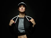 Woman athlete holding resistance band against black background Royalty Free Stock Images