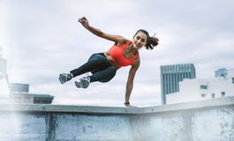 Woman athlete jumping onto the rooftop from the fence. Fitness woman jumping on to the terrace from the rooftop fence with one hand on fence. Woman in fitness stock image