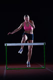 Woman athlete jumping over a hurdles Stock Photo