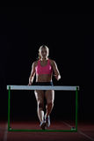 Woman athlete jumping over a hurdles Stock Images