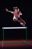 Woman athlete jumping over a hurdles Royalty Free Stock Photography