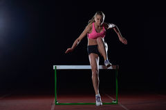Woman athlete jumping over a hurdles Royalty Free Stock Photo