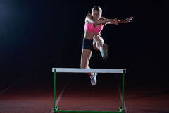 Woman athlete jumping over a hurdles Stock Photos