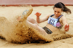 Woman athlete landing in sand long jump Stock Images