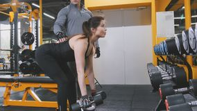 Woman athlete lifting dumbbells in the gym - close up. View Royalty Free Stock Image