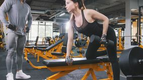 Woman athlete lifting dumbbells in the gym - coach observing training Royalty Free Stock Photography