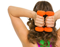 Woman athlete making exercise with dumbbells . rear view Royalty Free Stock Photography