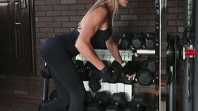 Woman performs one arm bent-over dumbbell row exercise stock video footage