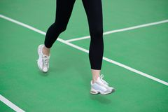 Woman Athlete Runner Feet Running on Green Running Track. Fitness and Workout Wellness Concept. Royalty Free Stock Images