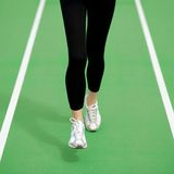 Woman Athlete Runner Feet Running on Green Running Track. Fitness and Workout Wellness Concept. Stock Photo
