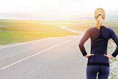 Woman athlete runner getting ready to run in beautiful nature mountain landscape.  Jogging, sport, fitness, active lifestyle conce Stock Image
