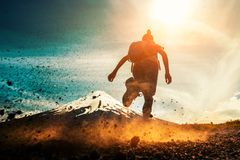Woman athlete runs. On a dirty and dusty ground with volcano on the background. Trail running athlete working out in the mountains Stock Photo