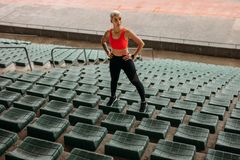 Woman athlete standing on the seats in the stands stock photography