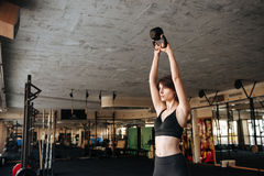 Woman athlete standing and wotking out with kettlebell in gym Stock Photography