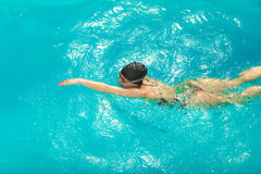 Woman athlete swimming crawl stroke in pool. Stock Photos