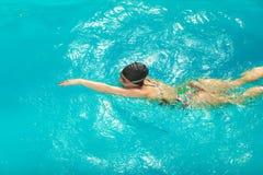 Woman athlete swimming crawl stroke in pool. Stock Photos