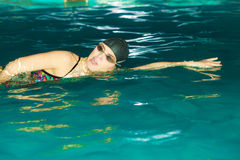 Woman athlete swimming crawl stroke in pool. Woman athlete swimming performing crawl style stroke in pool. Active human swimmer taking breath. Water sport Stock Photos