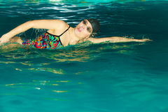 Woman athlete swimming crawl stroke in pool. Stock Photo