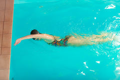 Woman athlete swimming crawl stroke in pool. Stock Images