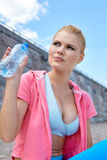 Woman athlete takes a break, she drinking water Royalty Free Stock Photography