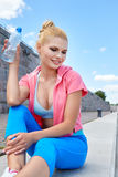 Woman athlete takes a break, she drinking water Royalty Free Stock Images