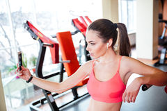 Woman athlete taking selfie and listening to music in gym. Pretty young woman athlete taking selfie and listening to music from cell phone in gym Stock Photography