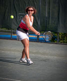 Woman athlete about to hit a tennis ball Stock Photos