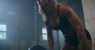 The woman athlete trains in the gym, raises the bar. Strength is power. Muscular female shirtless athlete doing deadlift