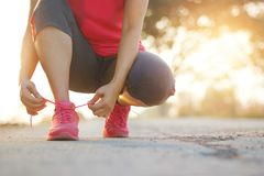 Female athlete tying running shoes on rural street in sunset back. Woman athlete tying running shoes on rural street at sunset background. Sport lifestyle Royalty Free Stock Photo