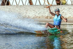 Woman athlete on a wakeboard. Woman is an extreme sportswoman on a wakeboard on the water Stock Photos