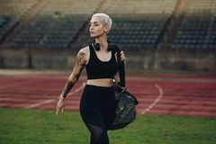 Woman athlete walking inside a track and field stadium. Female runner walking in a track and field stadium carrying her bag. Woman in fitness wear walking in a stock photo